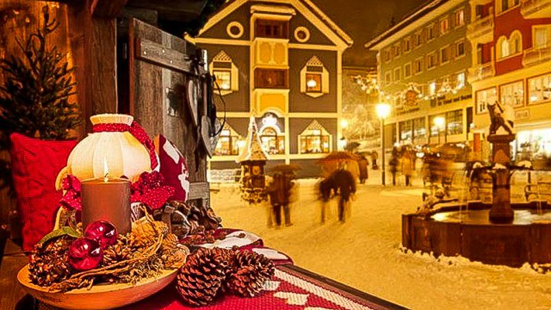 дом уют горнолыжный курорт зимний городок вечер вид из окна люди гуляют приятная атмосфера недвижимость в италии север недвижимость в горах в италии